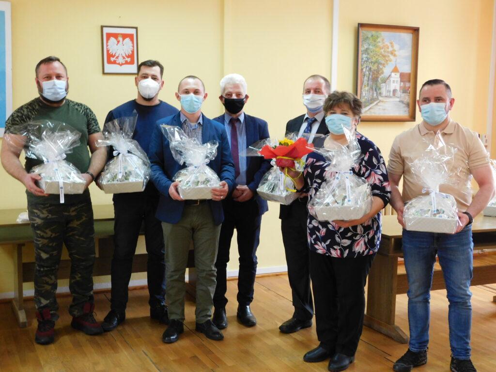 Zdjęcie przedstawiające sześciu panów sołtysów ijedną panią sołtys trzymających wdłoniach upominki zapakowane wcalofan orazwśrodku pana wójta, wszyscy mają natwarzach maseczki, wtle godło Polski iobraz przedstawiający urząd gminy.