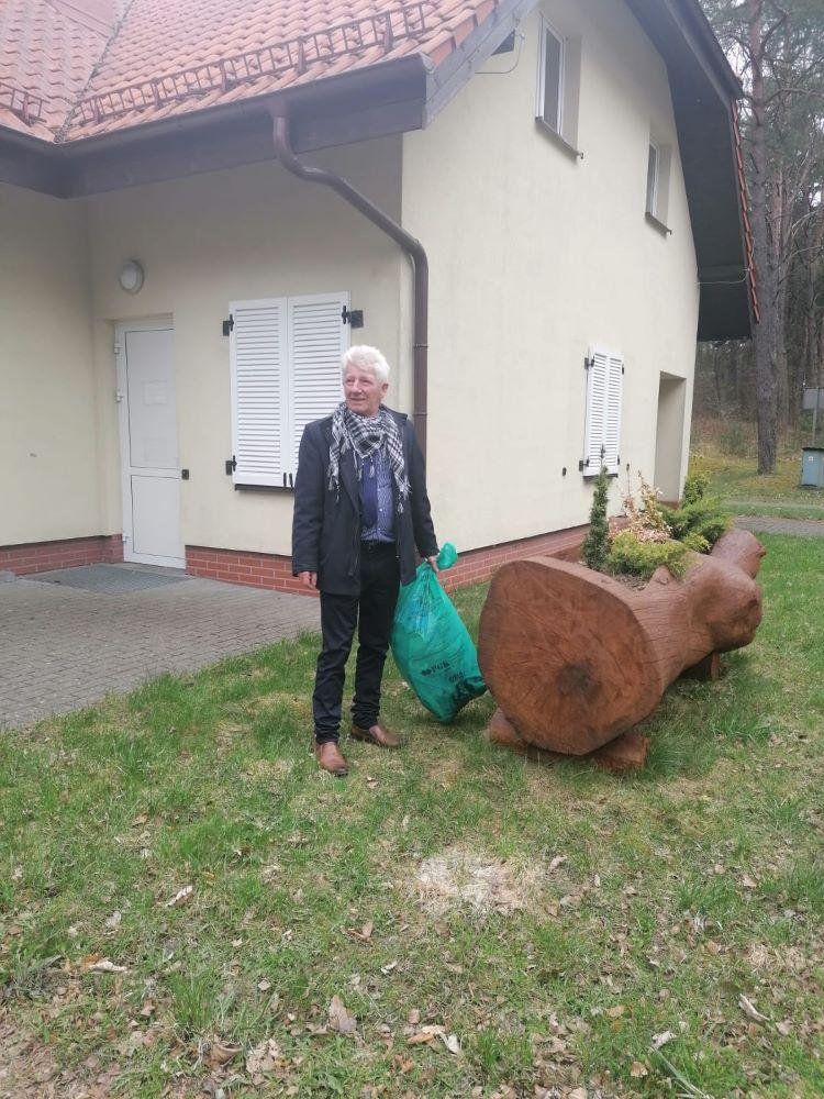 Wójt gminy Koczała natle kompleksu wypoczynkowego nadjeziorem Dymno, zworkiem pełnym śmieci.