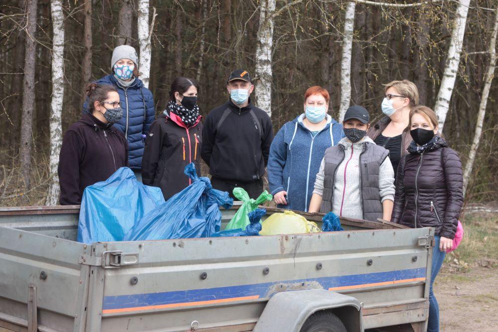 Worki pełne śmieci wrzucone naprzyczepkę, wtle pracownicy urzędu gminy Koczała.