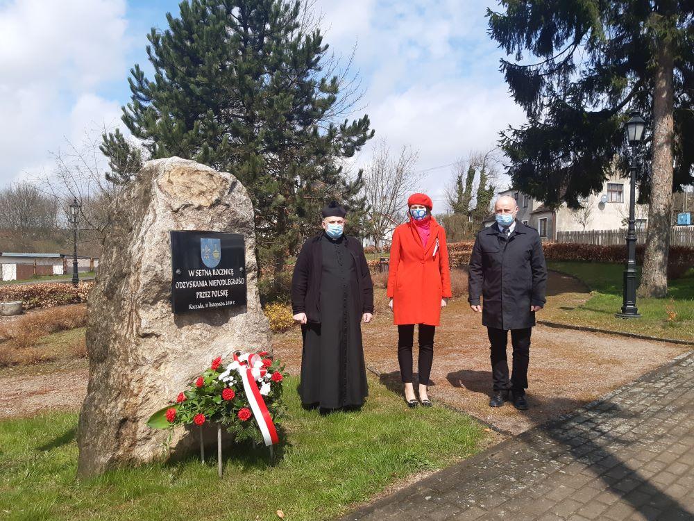 Delegacja władz gminy orazksiądz proboszcz podobeliskiem upamiętniającym setną rocznicę odzyskania niepodległości przezPolskę. Podobeliskiem kwiaty.