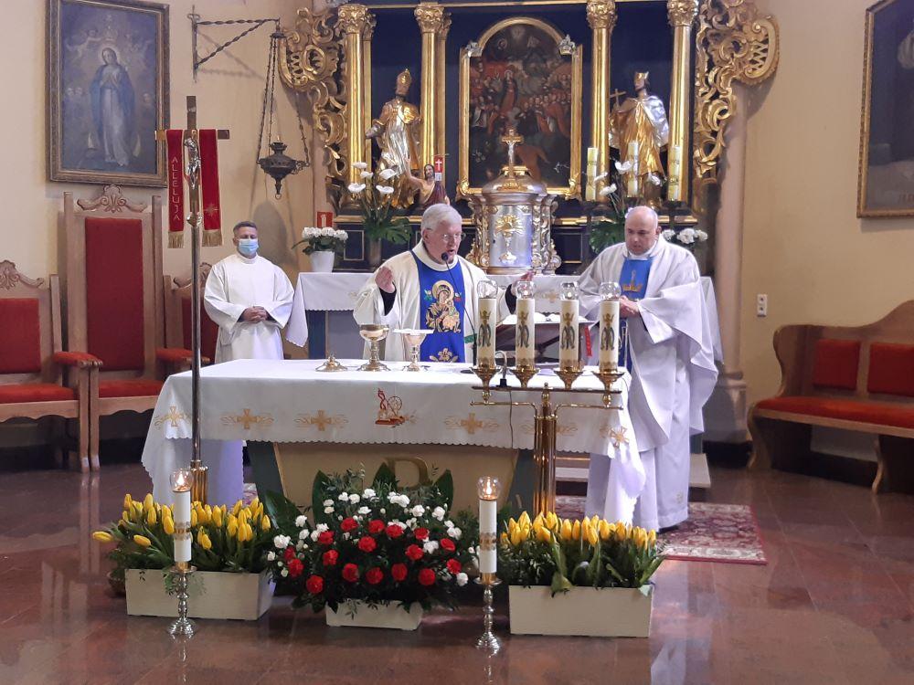 Zdjęcie przedstawiające ołtarz wraz zcelebransami mszy świętej. Zprzodu kwiaty, awtle ołtarz główny kościoła parafialnego wKoczale.