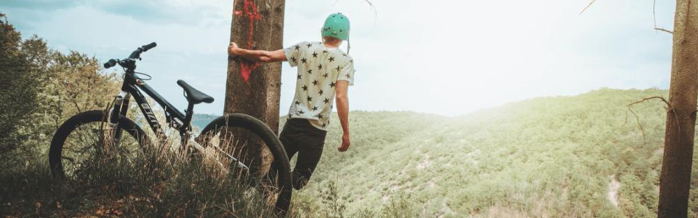 Fotografia przedstawia rower orazrowerzystę zkaskiem nagłowie. Rowerzysta obejmuje ręką pień drzewa. Wtle słońce chowające się zapagórkowatym horyzontem.