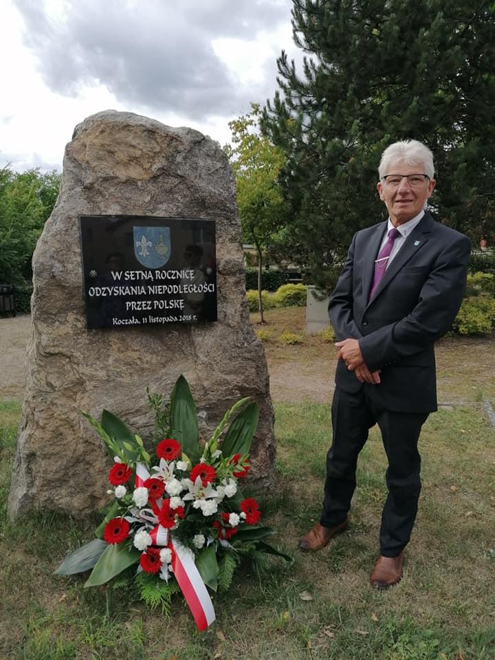 Wójt Gminy Koczała podobeliskiem upamiętniającym setną rocznicę odzyskania niepodległości przezPolskę. Podobeliskiem kwiaty wkolorach narodowych.