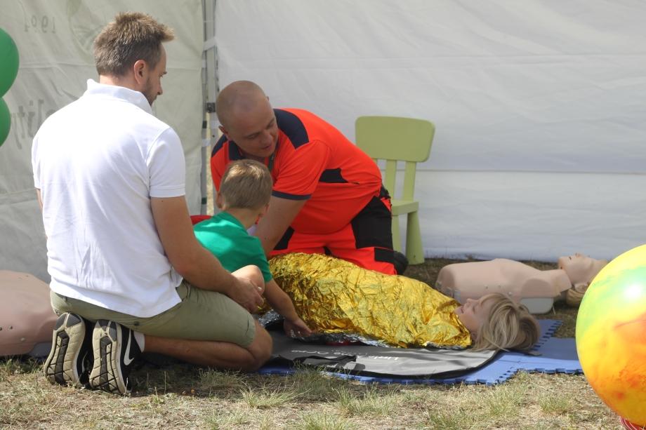 Fotografia przedstawia ratownika medycznego prowadzącego instruktarz zawijania dziecka wkoc termiczny. Obok mężczyzna ichłopiec.