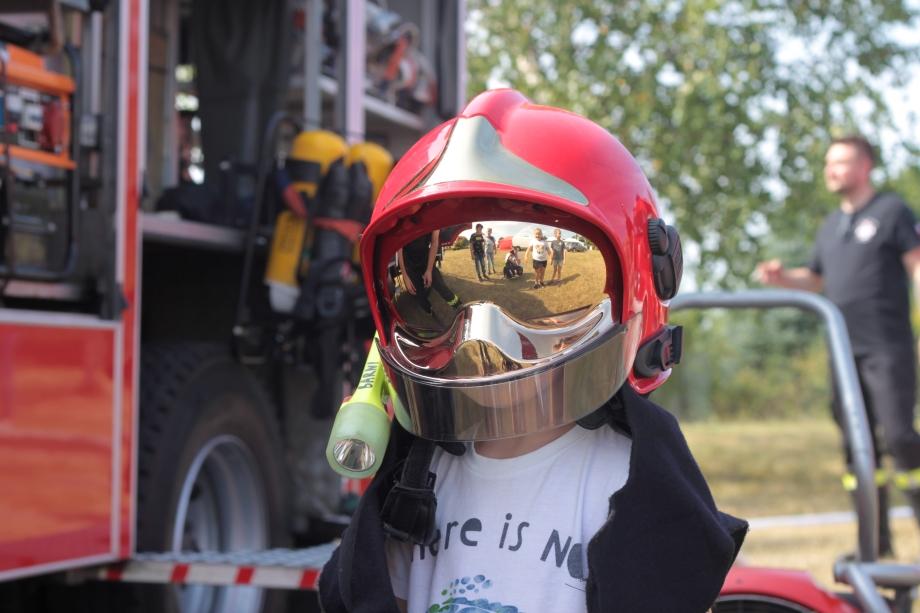 Fotografia przedstawiająca chłopca whełmie strażackim.