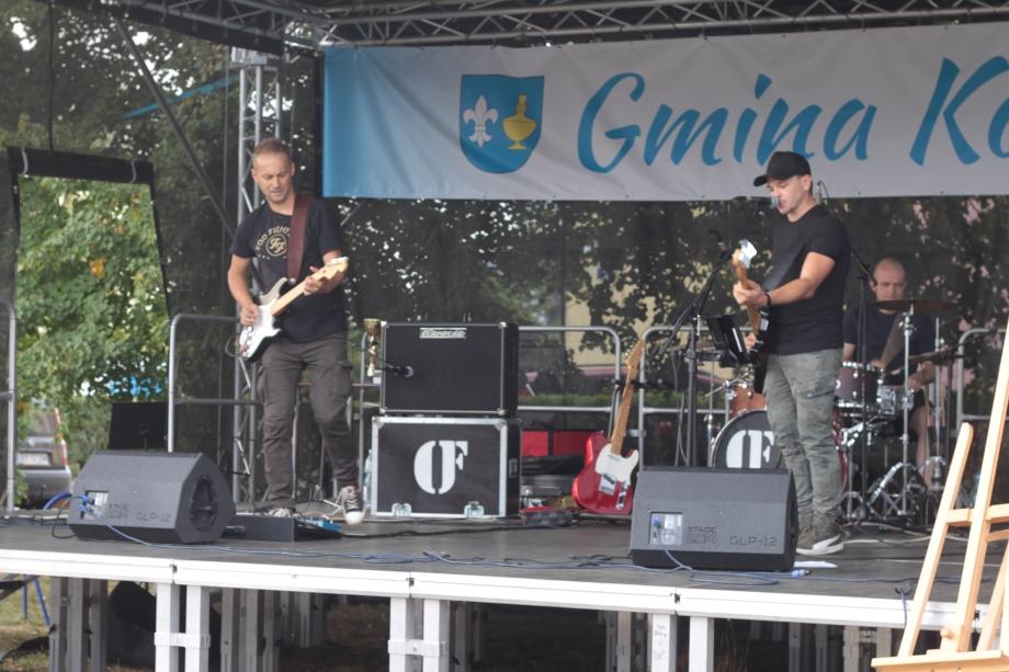 Fotografia przedstawiająca występ zespołu rockowego nascenie. Polewej gitarzysta, poprawej wokalista igitarzysta, ztyłu perkusista.