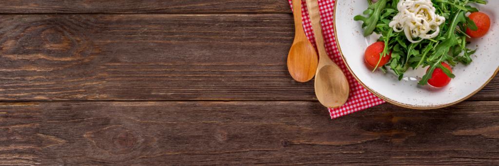 Grafika przedstawiająca talerz zezdrowym jedzeniem, obok serwetka idrewniane łyżki.
