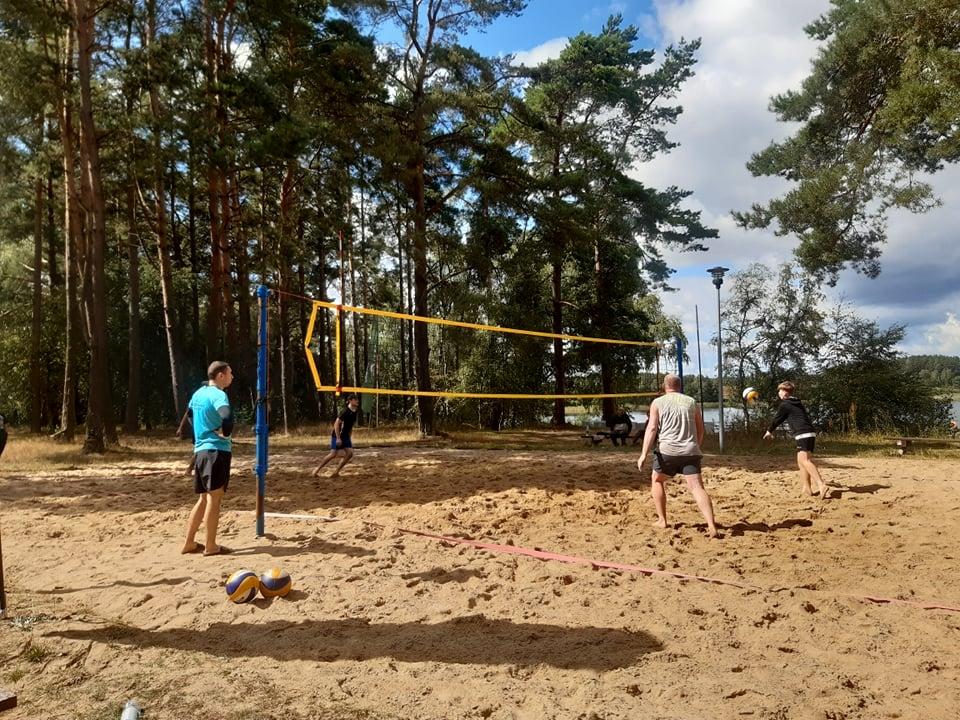 Widok naboisko dosiatkówki plażowej orazrozgrywającego zawodnika. Wtle jezioro Dymno, baner zlogotypem sponsora Goodvalley.