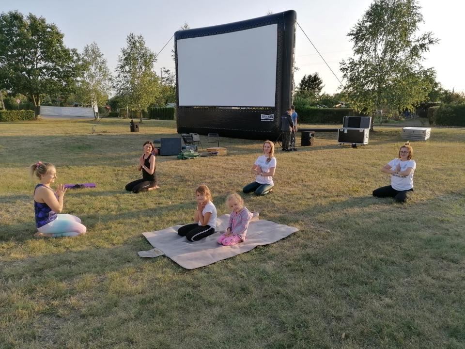 Pole naplac rekreacyjny ićwiczące jogę kobiety. Wtle brzozy, ogródki działkowe iekran kina plenerowego.