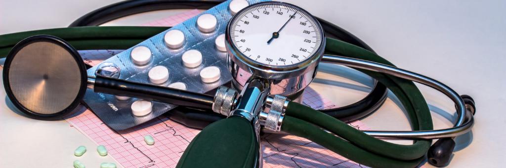 Grafika przedstawiająca ciśnieniomierz, stetoskop, wydruk EKG itabletki.